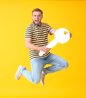 Jumping young man with big paper key on color background