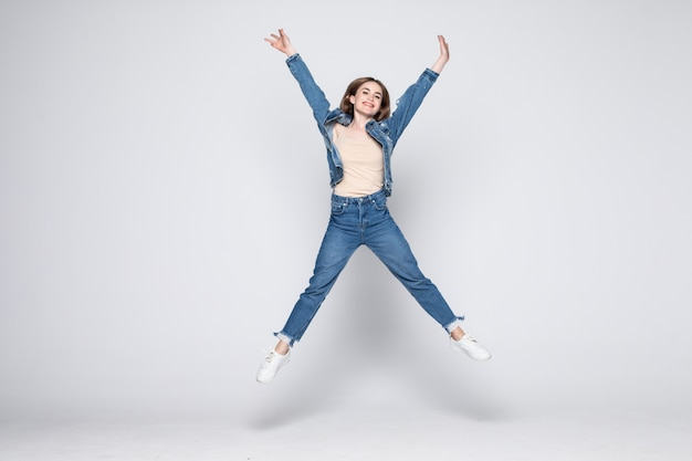 Jumping young woman in jeans on white wall