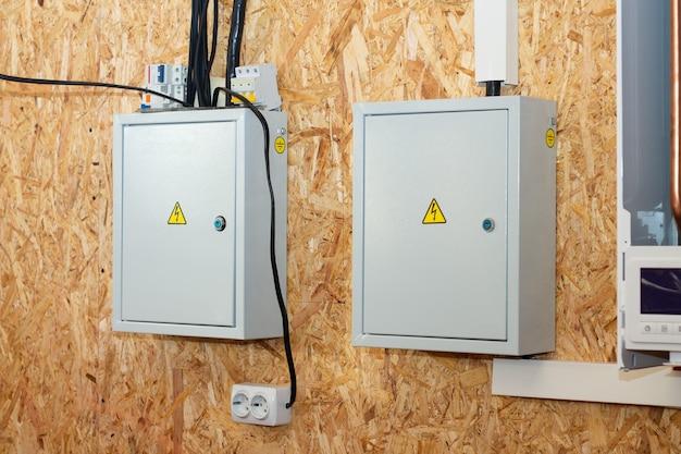 Распределительные коробки с электрическими выключателями внутри строящегося дома на стене, облицованной osb, ориентированно-стружечной плитой