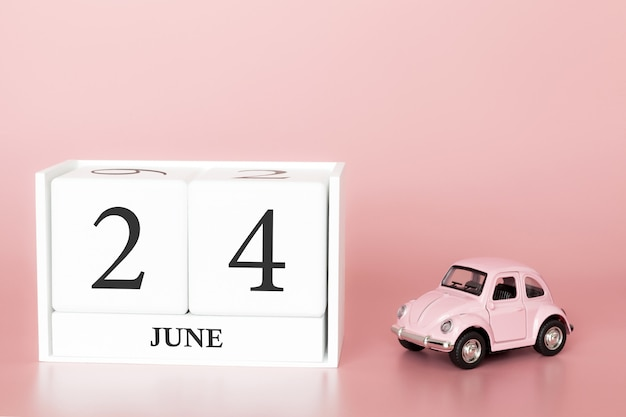 June 24th, day 24 of month, calendar cube on modern pink background with car