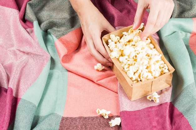 June celebration. hand taking popcorn on a colored fabric.