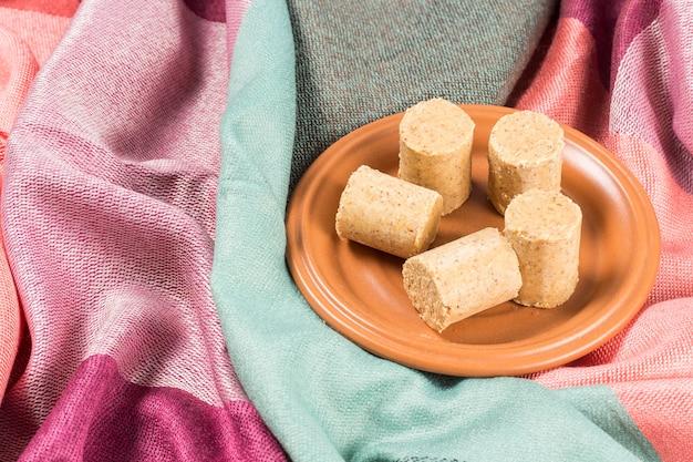June celebration. sweet brazilian peanut called paã§oca on a plate on a colored fabric..