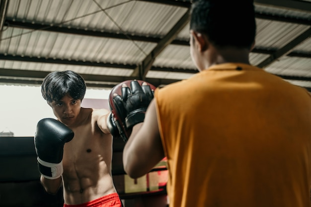 Junior boxer and coach training together with punching pads on the boxing ring at training camp