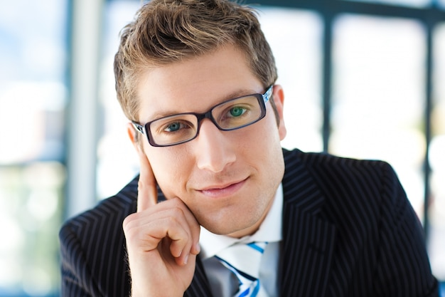 Junior businessman looking to the camera wearing glasses