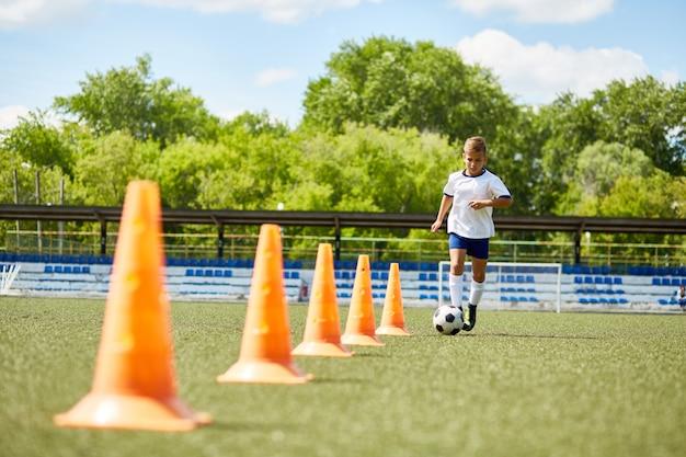 Юный футболист тренируется с мячом