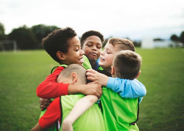 お互いを抱きしめるジュニアサッカーチーム