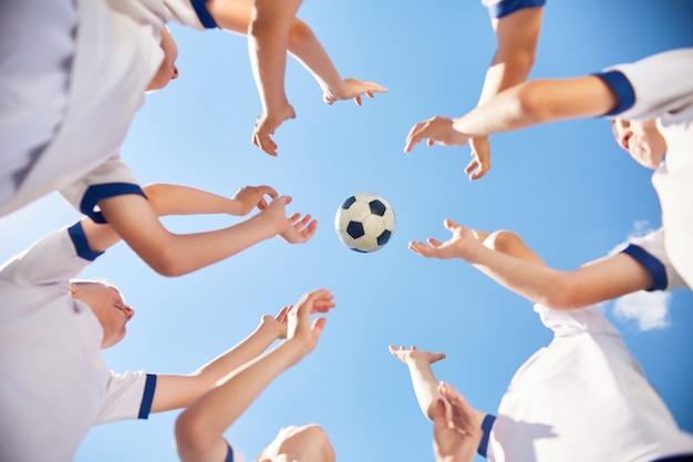 Юношеская футбольная команда бросает мяч