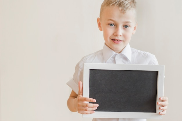 Junior holding chalkboard in studio