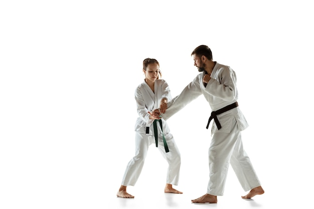 Junior in kimono practicing hand-to-hand combat with coach