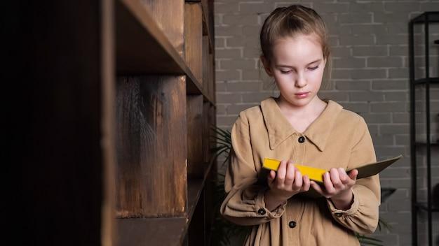 주니어 학생 여성은 큰 갈색 나무 책장에 접근하고 큰 오래된 책을 선택하고 도서관의 회색 벽돌 벽에 읽기 시작합니다
