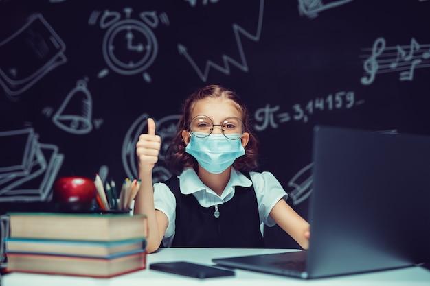 의료용 마스크를 쓴 주니어 학생은 엄지손가락을 보여주는 노트북에서 온라인 가상 학습 언어 수업