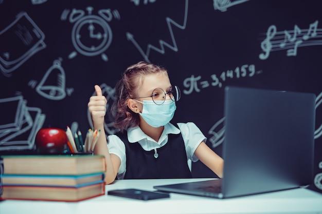 Младший студент в медицинской маске онлайн-класс виртуального изучения языка на ноутбуке, показывая большой палец вверх