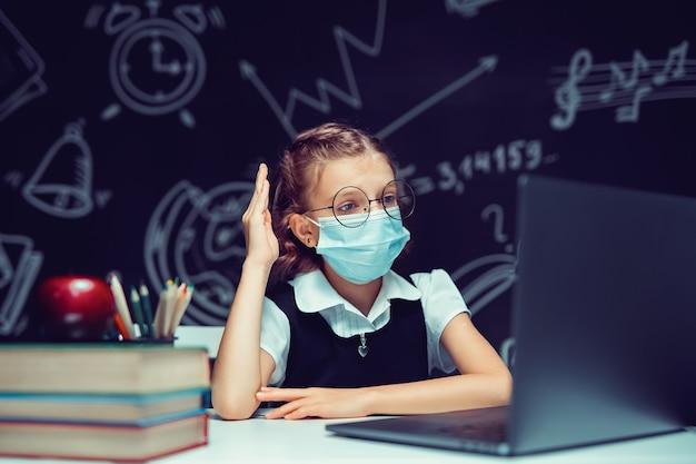의료용 마스크를 쓴 주니어 학생 노트북으로 온라인 가상 학습 언어 수업