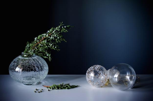 Ветки можжевельника в стеклянной вазе и новогодние шары на синем фоне