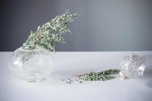 Ветки можжевельника в стеклянной вазе и новогодние шары на сером фоне