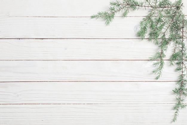 Ветви можжевельника на белом фоне деревянных. рождество и новый год фон
