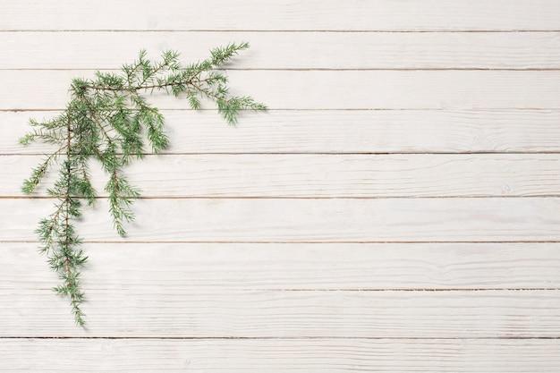 Ветви можжевельника на белом фоне деревянных. рождество и новый