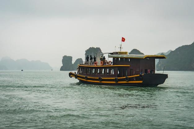 ベトナムのハロン湾の水に浮かぶジャンクボート。観光、アジアの旅行者のための活動。ベトナムの海