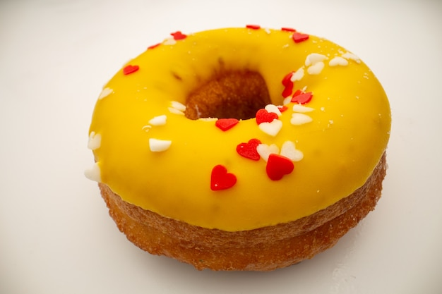 ジャンクフードのコンセプト-黄色い釉薬をかけた大きなドーナツ。