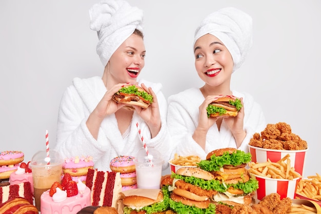 Junk food consuming. positive two women best friends eat delicious hamburgers stand closely to each other surrounded by different tasty high calorie snacks