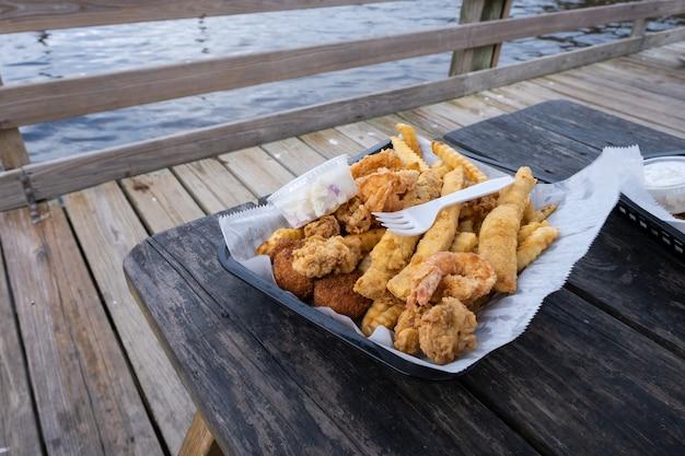 Вредная еда. хрустящая рыба, креветки и чипсы. жареные морепродукты, картофель фри, дольки лимона в одноразовой посуде в ресторане в порту.