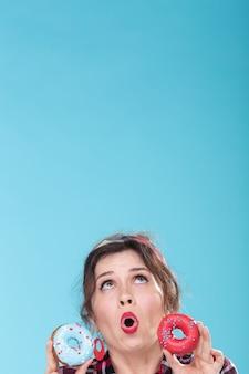 ジャンクフード、ダイエット、不健康なライフスタイルのコンセプト-青い表面にドーナツを持ったピンナップ女性