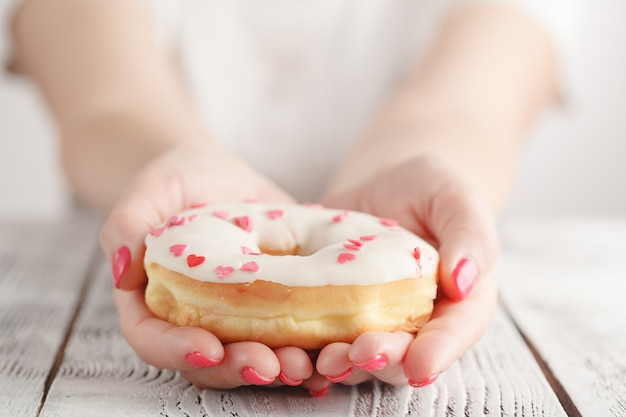 Junk-food and eating concept - close up of female hand holding glazed donut