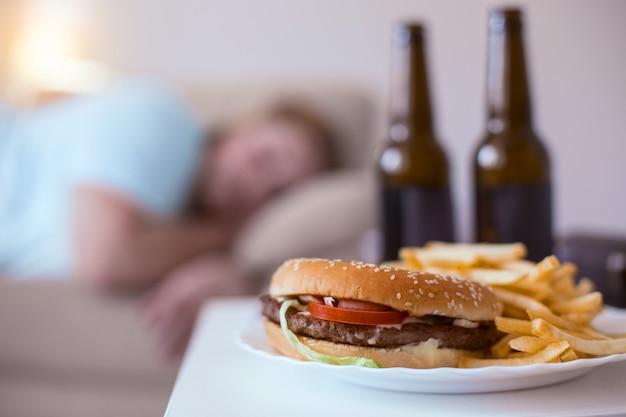 Вредная еда. жирный гамбургер с картофелем фри, лежащий на тарелке