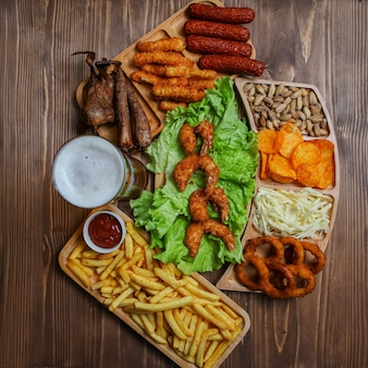 Junk food products in wooden plates with beer, cheese, barbecue, pistachio top view