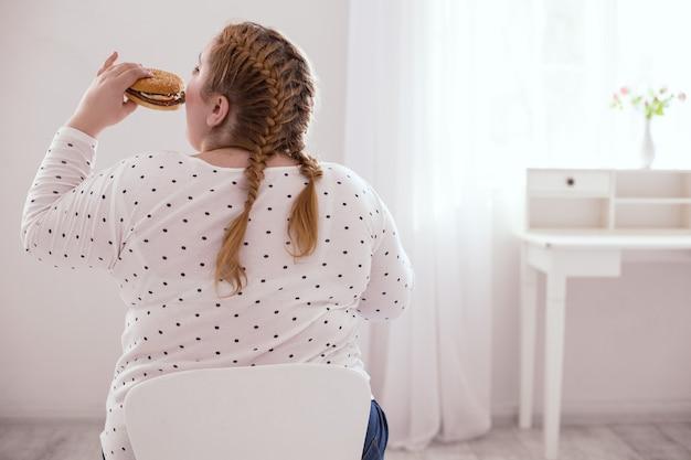 Вредная еда. отвернутая полная женщина ест гамбургер, сидя на стуле