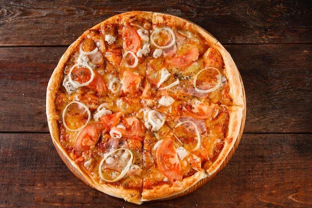 Нездоровая пища, нездоровое питание, вредные привычки, калорийность. горячая свежая запеченная пицца с ветчиной, луком, помидорами и сыром подается на темном деревянном столе, плоская кладка.