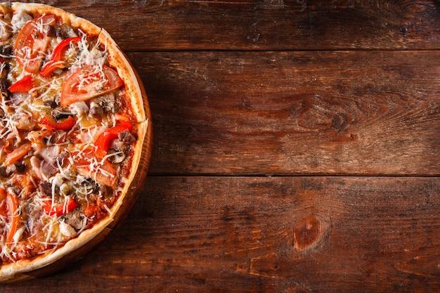 Нездоровая пища, нездоровое питание, вредные привычки. свежая итальянская пицца с ветчиной, грибами, помидорами и сыром подается на деревянном столе. темный фон со свободным пространством для текста.