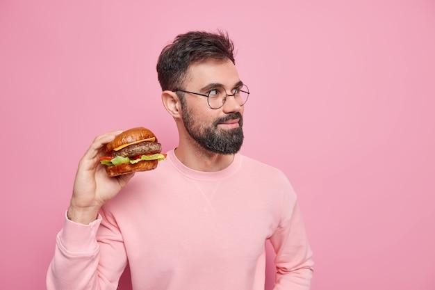 Cibo spazzatura e concetto di nutrizione malsana. l'uomo adulto barbuto tiene in mano un delizioso hamburger ha uno spuntino veloce distoglie lo sguardo pensieroso