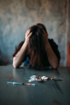 Наркоман сидит за столом с наркотиками и шприцем