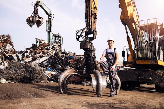 고철 부품을 들어 올리는 데 사용되는 유압 산업 기계 옆에 서 있는 폐차장 작업자