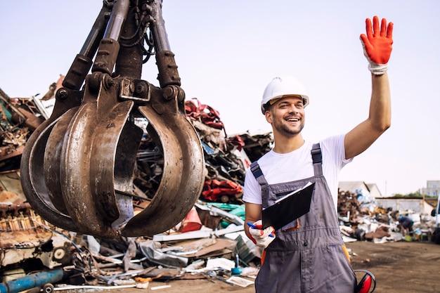 고철 부품을 들어 올리기 위해 크레인 작업자에게 손을 흔드는 폐차장 작업자.