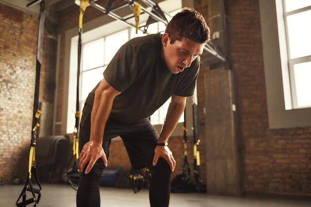 1분만 쉬세요. 체육관에 서 있는 동안 지쳐 보이는 운동복을 입은 젊은 운동 남자