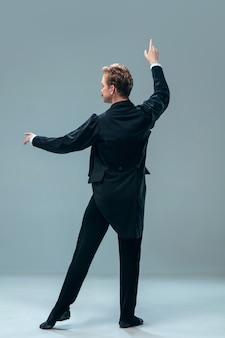 잠시만. 회색 스튜디오 배경에 고립 된 아름 다운 현대 볼룸 댄서. 왈츠, 탱고, 슬로우 폭스, 퀵 스텝을 춤추는 감각적 인 프로페셔널 아티스트. 유연하고 무중력.