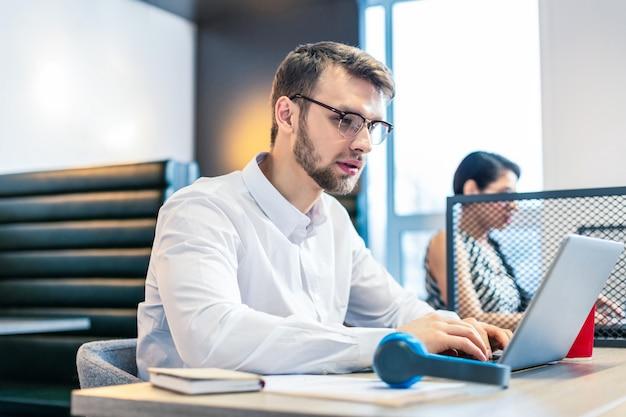 Просто внимание. сосредоточенный бородатый мужчина в стильных очках за ноутбуком