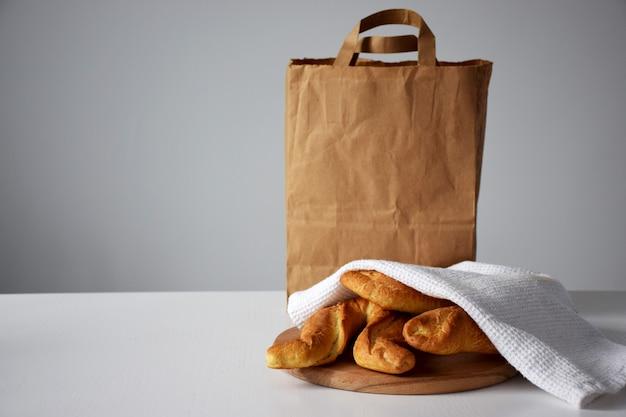 나무 커팅 보드에 흰색 주방 수건 아래에 구운 빵과 배달 서비스를위한 종이 패키지
