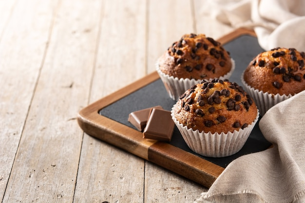 Just baked chocolate muffins on wooden table