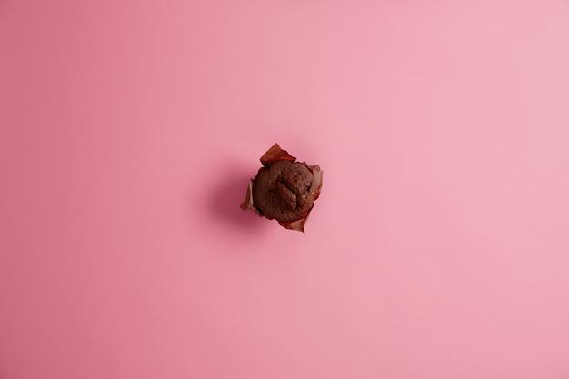 Только что испеченный вкусный сладкий шоколадный кекс в оберточной бумаге, сфотографированный сверху, изолированный на розовом фоне, готовый к употреблению. нежелательная еда, десерты, калории и концепция питания. селективный фокус