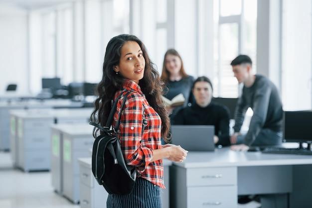 Только что пришла сюда. группа молодых людей в повседневной одежде, работающих в современном офисе