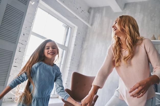 Просто танцуй! мать и дочь держатся за руки и улыбаются, танцуя в спальне