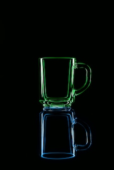 Just a glass on a black background with a reflection. green and blue colors. isolated.