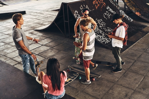 그냥 친구들과 어울려. 야외 스케이트 공원에서 시간을 보내는 동안 함께 어울리는 스케이터 친구들의 상위 뷰