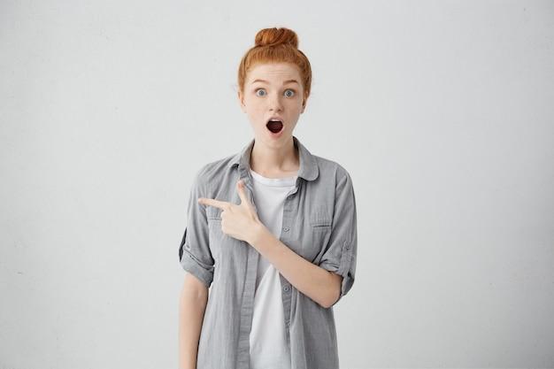 見てください!指で空白の壁に何かを見せて驚いたり衝撃を与えたりした感情的な虫眼鏡の10代の少女。