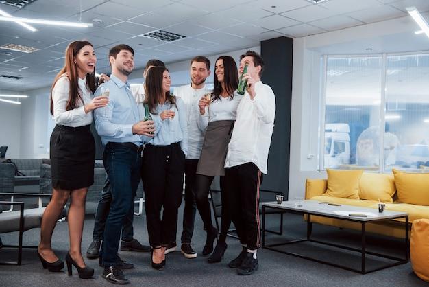 ただ冗談を言う。モダンな明るいオフィスで飲み物を保持している古典的な服の若いチームの写真