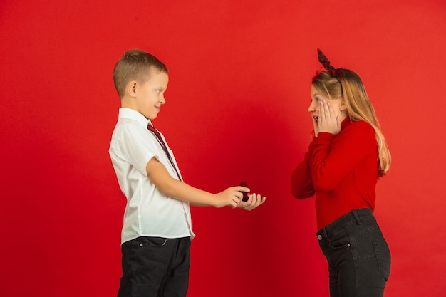 Just like grown-up. valentine's day celebration, happy, cute caucasian kids isolated on red studio background. concept of human emotions, facial expression, love, relations, romantic holidays.