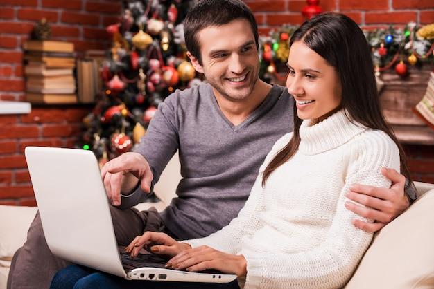 그것만 봐! 남자가 모니터를 가리키고 백그라운드에서 크리스마스 장식으로 웃고 있는 동안 컴퓨터를 함께 사용하는 아름다운 젊은 부부